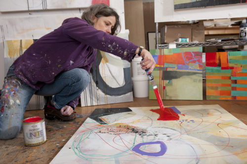 Jane Davies painting in her studio